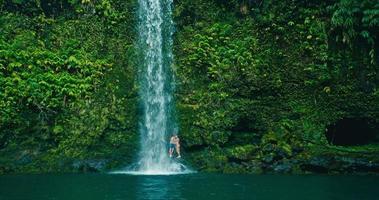 casal relaxando sob a cachoeira