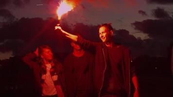 grupo de adolescentes felices con uno sosteniendo y agitando una bengala de señal caminando hacia la cámara por la noche. video
