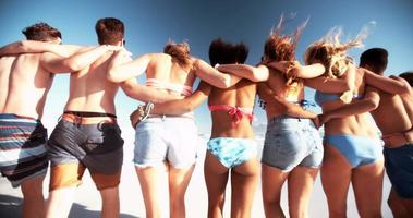 amigos caminhando juntos na praia no verão