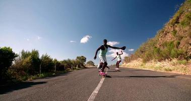 grupo racial misto de skatistas adolescentes correndo ladeira abaixo
