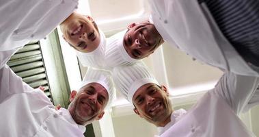 équipe de chefs debout en cercle regardant la caméra