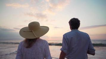 concepto de vacaciones de jubilación, feliz pareja de jubilados maduros disfrutando de la hermosa puesta de sol en la playa