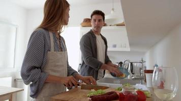 Young adult couple talking as they prepare food and wash up, shot on R3D video
