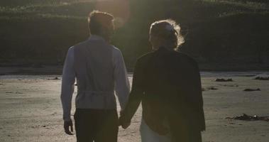 sonrientes recién casados caminando juntos en la playa