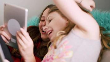 jugendliche Freunde, die ihre Tablets zu Hause zusammen benutzen