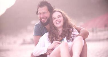 jovem casal sentado amorosamente na praia