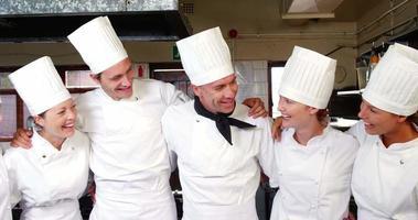 groep chef-koks staan samen met armen rond video