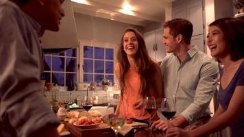 Parejas de raza mixta riendo y preparando la cena juntos. video