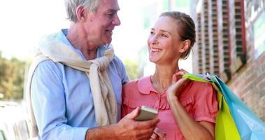 coppia felice guardando smartphone insieme in viaggio di shopping