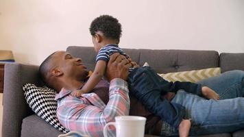 padre e figlio che si rilassano sul divano a casa insieme
