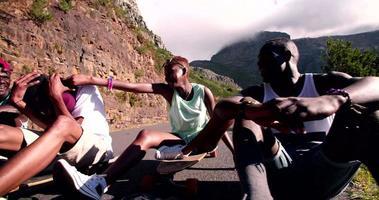 gemischte rassische Gruppe von jugendlichen Longboardern, die glücklich zusammensitzen