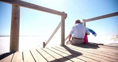 Elderly retired couple sitting together affectionately at the beach