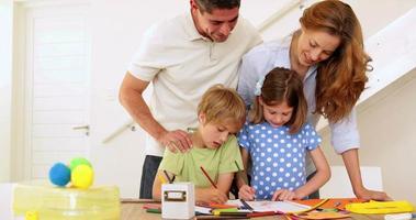 genitori e figli felici che disegnano insieme al tavolo