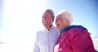 älteres Ehepaar im Ruhestand, das glücklich zusammen am Strand spazieren geht