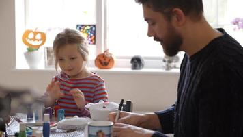 padre e figlia che fanno maschere di halloween a casa insieme