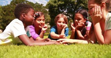 Élèves mignons allongés sur l'herbe avec les mains ensemble