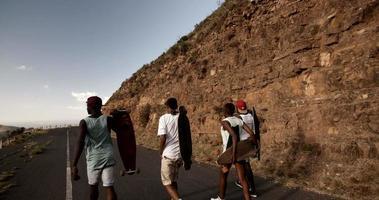 cool gruppo di skateboarder adolescenti che camminano insieme lungo la strada