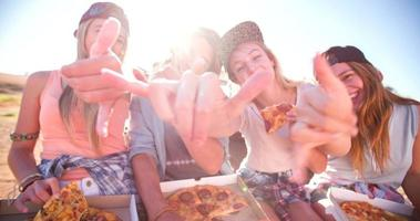 Teen friends eating pizza together outdoors with sun flare