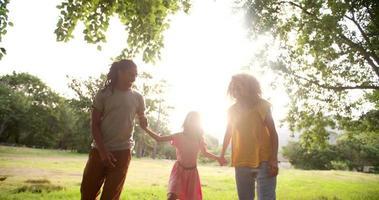 Afroamerikanerfamilie, die zusammen im schönen grünen Park geht