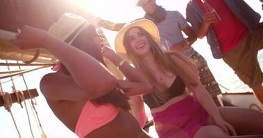 ragazze sorridenti su uno yacht a vela insieme a bevande estive