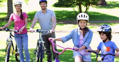 famiglia sorridente su un giro in bicicletta nel parco insieme