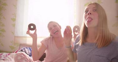 Teenager-Mädchen lachen und essen Donuts in einem Schlafzimmer zusammen