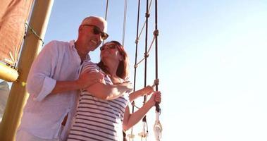 casal sênior em um cruzeiro de iate junto com o céu azul
