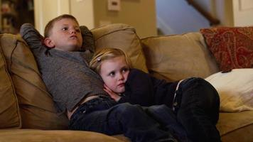 Young siblings sitting close together on the couch and watching television video