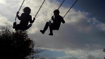 Siblings swinging in time together, slow motion, silhouette in the sky video