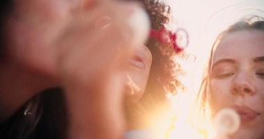 felice ragazza afro e amici in spiaggia che soffia bolle insieme al rallentatore video