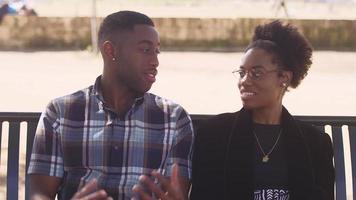 coppia afro-americana seduti insieme su una panchina sul lungomare della città e parlando