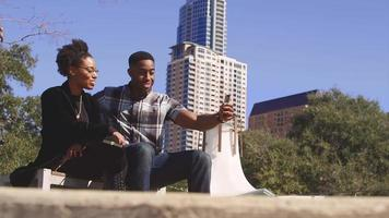 African American couple in front of city high rises, taking a cell phone picture together video