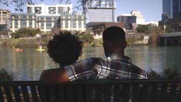 African American couple sitting together on a bench on the city waterfront, sunny, close up