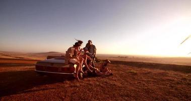 Jeunes amis adultes enjoing temps avec guitare au coucher du soleil