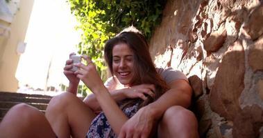 coppia seduta in un po 'di sole guardando un telefono insieme