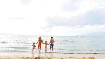 Familie läuft in und aus dem Ozean