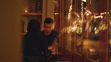 una giovane coppia che parla a una cena romantica, attraverso la finestra