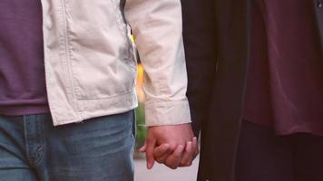una giovane coppia che cammina lungo un marciapiede e si tiene per mano