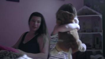 un bambino assonnato lascia la sua stanza con un peluche e si unisce alle sue sorelle sul divano