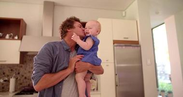 Modern Dad Holding and Kissing Infant Daughter on Cheek
