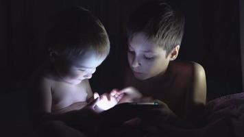 Two young brothers playing with tablet at night. 4K