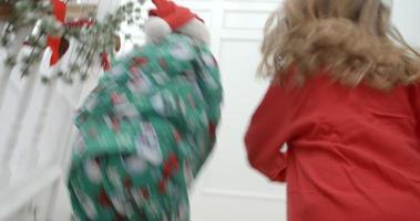 Toma de cámara lenta de niños en las escaleras en Nochebuena