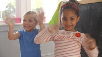 due ragazze di lavagna salutando la telecamera