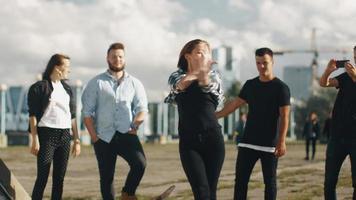 adolescente realizando dança moderna para grupo de amigos ao ar livre em ambiente urbano. video