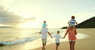 família feliz na praia ao pôr do sol