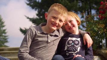 A young brother and sister smiling for a portrait on steps outside, slow motion video