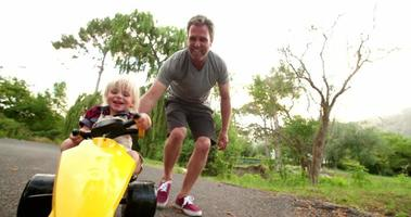 Happy dad pushing his laughing child in a toy car
