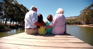 abuelos con sus nietos sentados en un embarcadero junto al lago