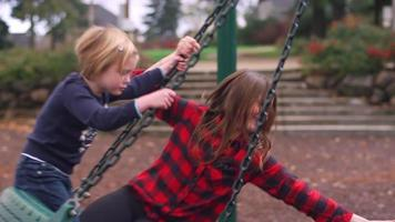 Three siblings play on a tire swing at the playground as their mom supervises video