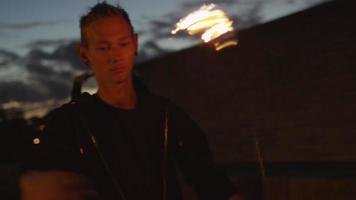 artista maschio che esegue spettacolo di fuoco all'aperto alla sera. video